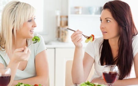 Joyful Women eating salad in a kitchen Stock Photo - 11191103