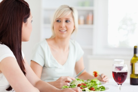 Portrait of happy Women eating salad in a kitchen photo