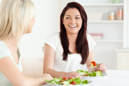Portrait of laughing Women eating salad in a kitchen photo