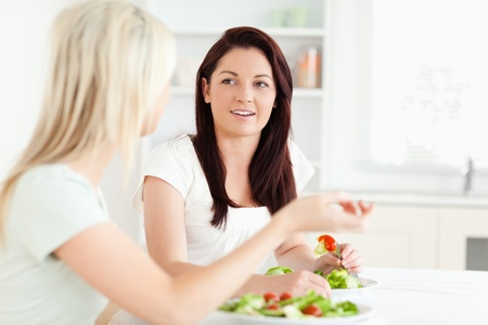 Portrait of young Women eating salad in a kitchen photo