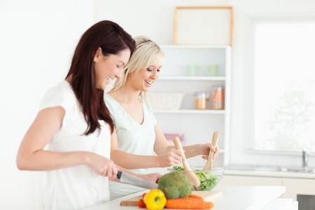 Joyful young Women preparing dinner in a kitchen photo
