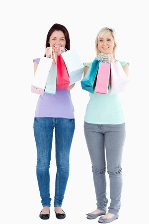 Charming women with shopping bags in a studio photo