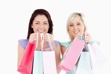 Smiling young women with shopping bags in a studio photo