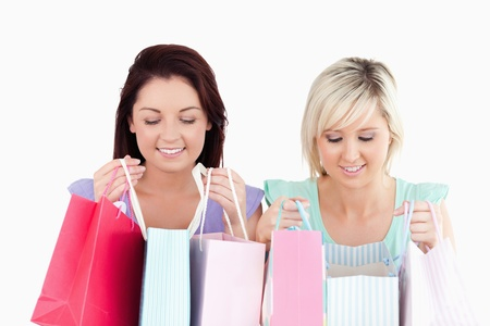 Happy young women with shopping bags in a studio photo