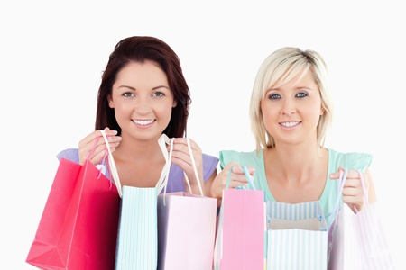 Cheerful young women with shopping bags in a studio photo