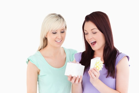 gifting: Blond woman gifting her friend in a studio