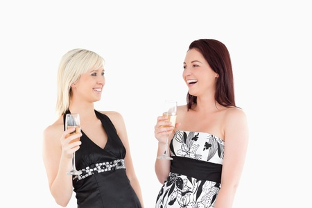 Smiling well-dressed women drinking champaign in a studio photo
