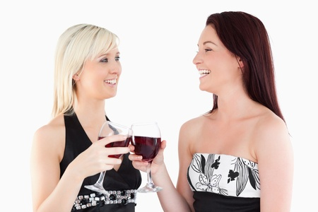 Laughing well-dressed women toasting with red wine in a studio photo