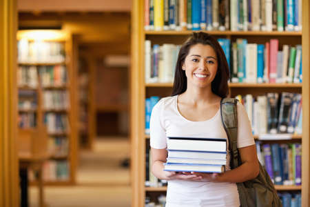 Student holding books in the library photo
