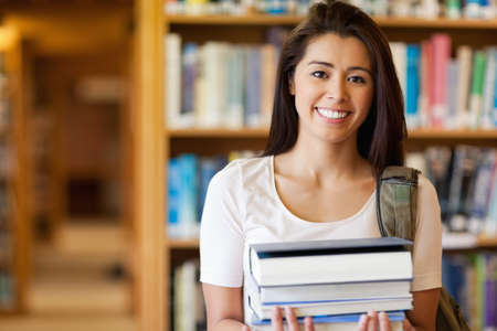 Smiling student holding books in the library photo