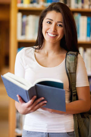 Portrait of a cute student holding a book in the library photo