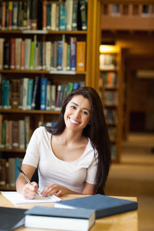 Portrait of a smiling student writing a paper in the library photo