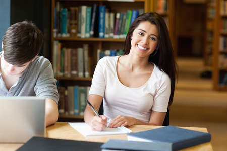 Smiling student writing a paper in the library photo