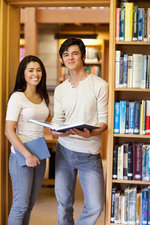 Portrait of students holding books in a library photo