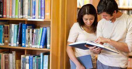 Smiling students looking at a book in a library photo