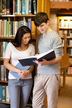 Portrait of young students reading a book in the library photo