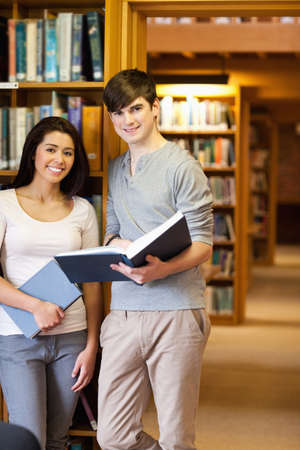 Portrait of young students with a book in the library photo