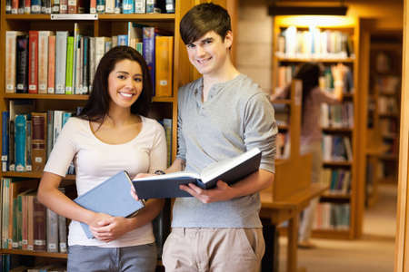 Beautiful students with a book in a library photo