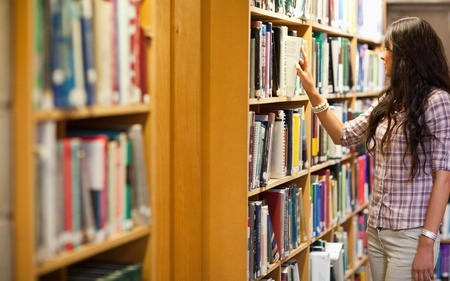 Young woman choosing a book in a library photo