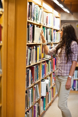Portrait of a young woman choosing a book in a library photo