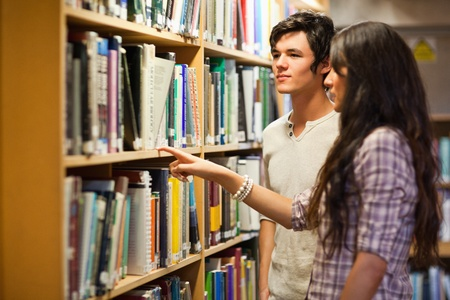 Students choosing a book in a library photo