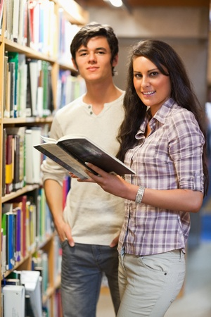 Portrait of young students holding a book in a library photo