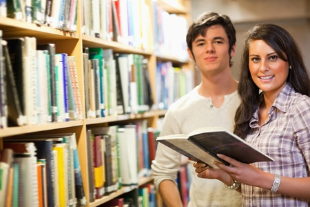 Young students holding a book in a library photo