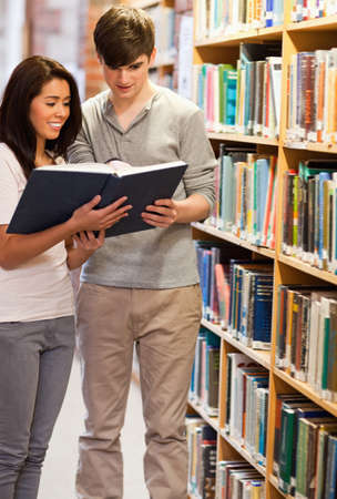 Portrait of happy students reading a book in a library photo