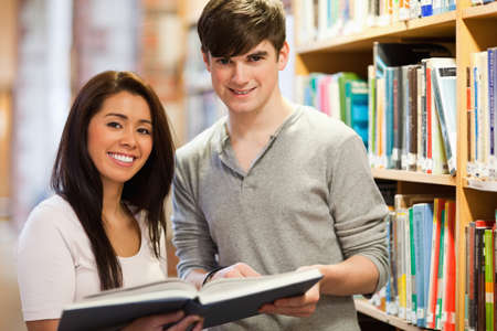 Happy students holding a book in a library photo