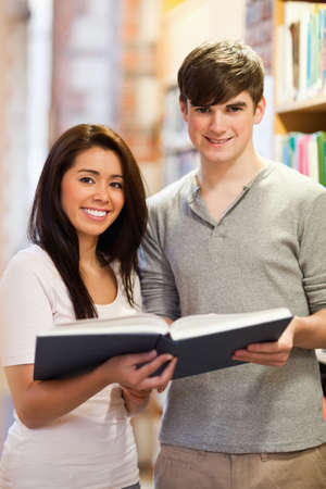 Portrait of good looking students with a book in a library photo
