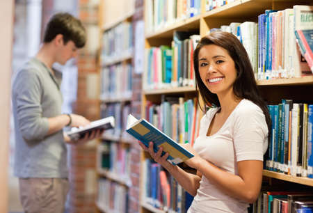 Good looking student holding a book in a library photo