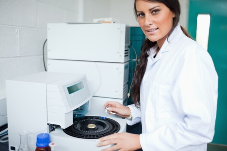 centrifuge: Serious laboratory assistant using a centrifuge while looking at the camera Stock Photo