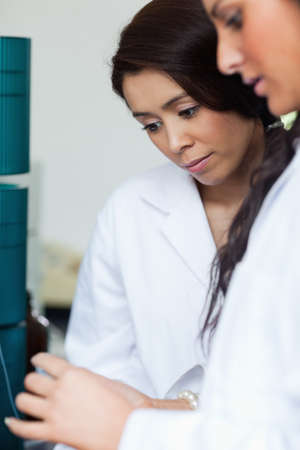 Portrait of students looking at a Petri dish in a laboratory photo