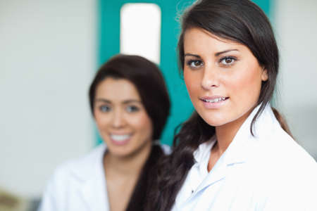 medical school: Beautiful female scientists posing with the camera focus on the foreground Stock Photo