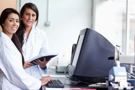 Smiling female scientist posing with a monitor while looking at the camera photo