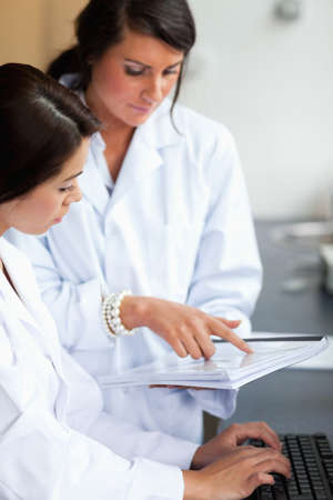 Portrait of female scientists looking at a report in a laboratory photo
