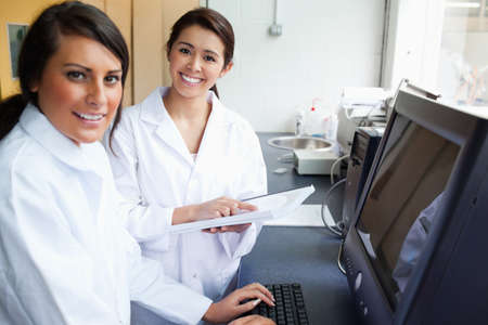 Smiling scientists posing with a monitor in a laboratory photo