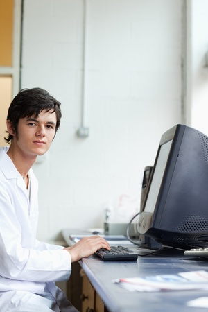 Portrait of a student posing with a monitor in a laboratory photo