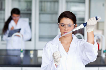 Female scientist pouring a liquid in a tube in a laboratory photo