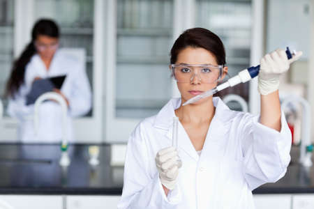 Serious female scientist pouring a liquid in a tube in a laboratory photo