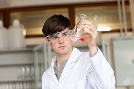 Scientist looking at a liquid in an Erlenmeyer flask in a laboratory photo