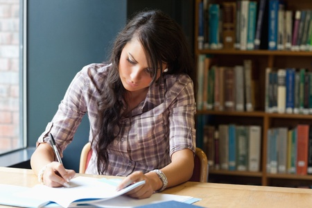 Young student writing in a library photo