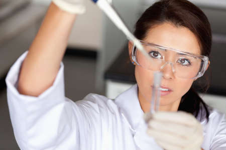 Brunette woman pouring a liquid in a tube in a laboratory photo
