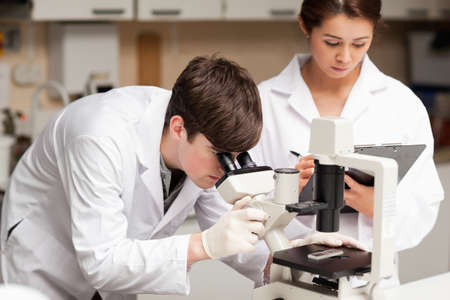 Scientist looking in a microscope while his colleague is taking notes in a laboratory photo
