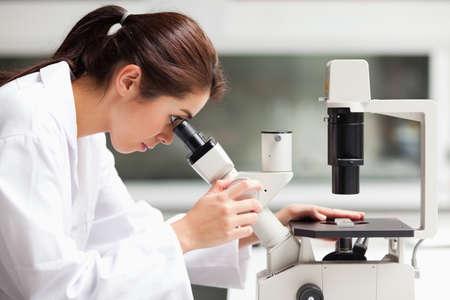 microscopio: Enfocado ciencia estudiante femenino que mira en un microscopio en un laboratorio