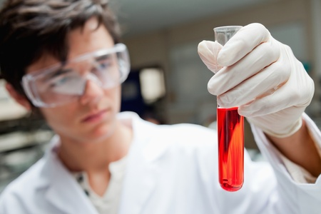 Young scientist holding a test tube in laboratory photo