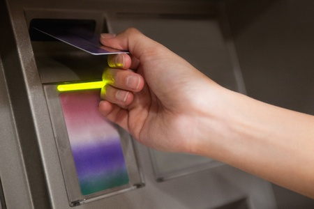 Close up of a hand inserting a credit card in an ATM photo