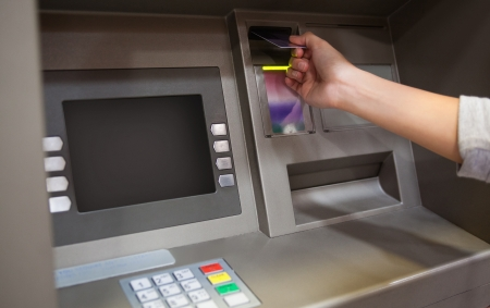 Hand inserting a credit card in an ATM photo