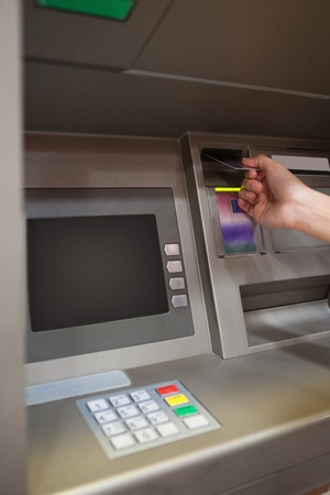 charge card: Portrait of a hand inserting a credit card in an ATM