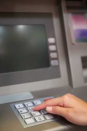 personal banking: Portrait of a hand typing a PIN code at an ATM